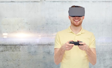 entertainment background: 3d technology, virtual reality, entertainment and people concept - happy young man with virtual reality headset or 3d glasses playing with game controller gamepad over gray concrete wall background