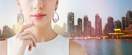 glamour luxury: glamour, beauty, jewelry and luxury concept - close up of beautiful woman face with pearl earrings over singapore city skyscrapers background
