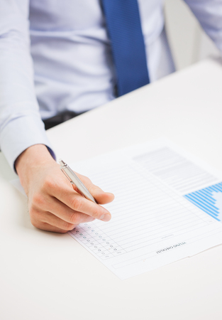 statistic: business, paperwork, statistics and people concept - close up of businessman hand with charts and pen filling form in office