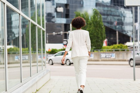 business and people concept - young african american businesswoman walking in city