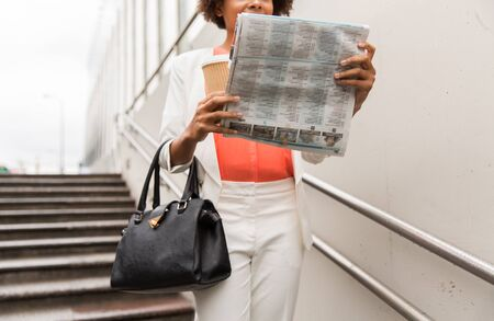 downstairs: business, drinks, lifestyle and people concept - close up of young african american businesswoman with coffee cup and newspaper walking downstairs to city subway
