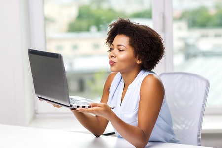 happy african: distant relationship, online communication and love concept - happy young african american woman sending kiss to laptop computer Stock Photo