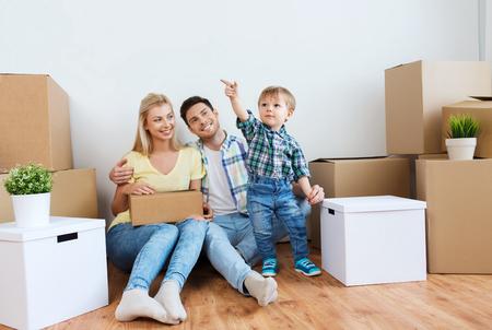 Hypothek, Menschen, Wohnen und Immobilien-Konzept - glückliche Familie mit Boxen auf neues Zuhause