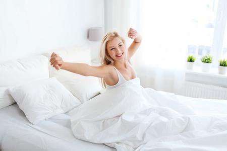отдых, сон, комфорт и люди концепции - молодая женщина, растяжения в постели у себя дома спальне Фото со стока