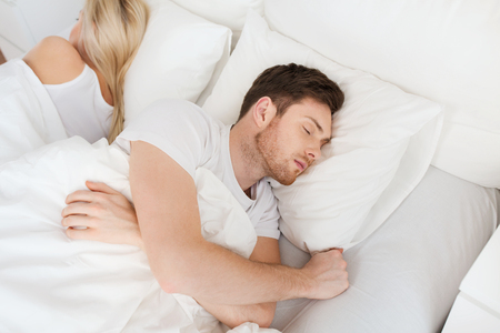 difficulties: people, relationship difficulties, conflict and family concept - couple sleeping back to back in bed at home Stock Photo