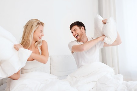 family fight: people, family, fun, bedtime and fun concept - happy couple having pillow fight in bed at home