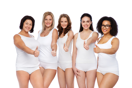 mid age: gesture, friendship, beauty, body positive and people concept - group of happy different women in white underwear showing thumbs up