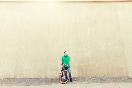 clavados: personas, estilo, ocio y estilo de vida - hombre inconformista joven feliz con la bici de piñón fijo en la calle de la ciudad