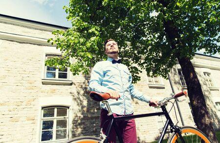 fixed: personas, estilo, ocio y estilo de vida - feliz joven inconformista montar en bicicleta de pi��n fijo en la calle de la ciudad Foto de archivo