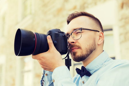 wide angle lens: people, photography, technology, leisure and lifestyle - happy young hipster man holding digital camera with wide angle lens taking picture on city street Stock Photo