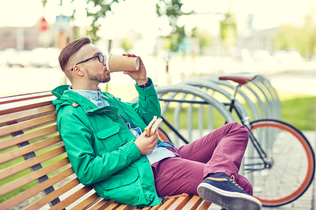 man eating: people, style, leisure and lifestyle - happy young hipster man drinking coffee cup and eating sandwich on city street