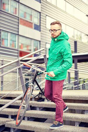 down stairs: la gente, el deporte, el estilo, el ocio y estilo de vida - hombre joven que lleva inconformista bicicleta fija del engranaje por las escaleras en la ciudad Foto de archivo