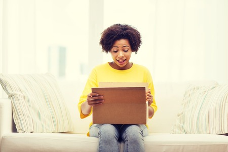 parcel: people, delivery, shipping and postal service concept - happy african american young woman opening cardboard box or parcel at home Stock Photo