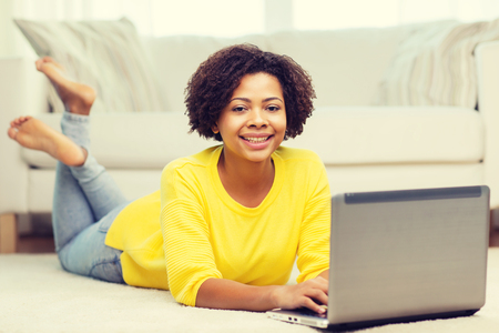 happy african: people, technology and leisure concept - happy african american young woman lying on floor with laptop computer at home Stock Photo