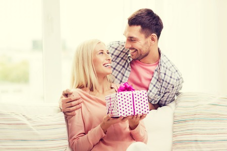 relationships, love, people, birthday and holidays concept - happy man giving woman gift box at home