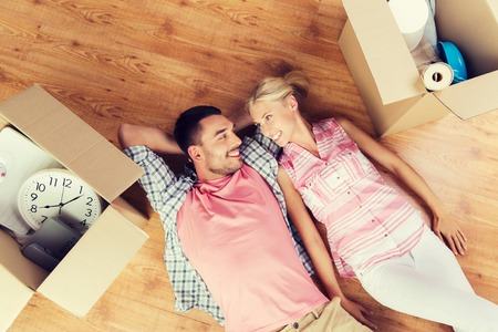 moving box: home, people, repair and real estate concept - happy couple with cardboard boxes and stuff lying on floor to new place Stock Photo