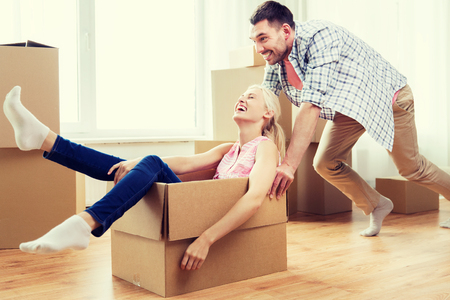 karton: home, people, moving and real estate concept - happy couple having fun and riding in cardboard boxes at new home