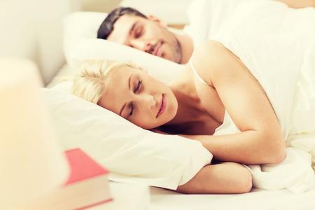 gente durmiendo: las personas, la familia, la hora de acostarse y el concepto de la felicidad - feliz pareja durmiendo en la cama en su casa Foto de archivo