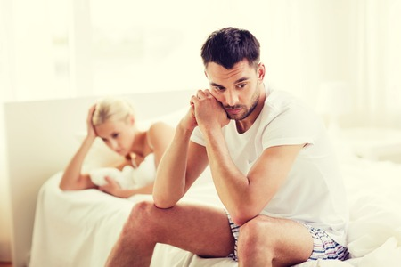people, relationship difficulties, conflict and family concept - unhappy couple having problems at bedroom Stock Photo