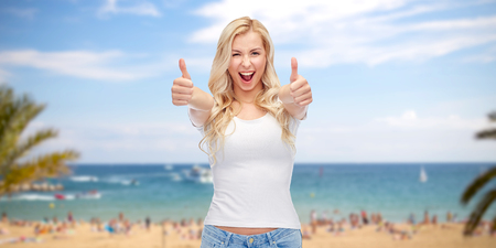 summer holidays: emotions, summer holidays, travel, advertisement and people concept - happy smiling young woman in white t-shirt showing thumbs up over exotic tropical beach with palm trees and sea background