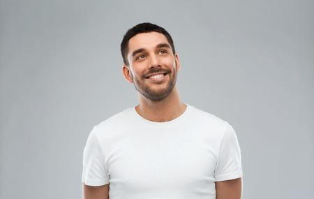 anuncio, la idea, la inspiración y el concepto de la gente - sonriente feliz joven mirando hacia arriba sobre gris Foto de archivo
