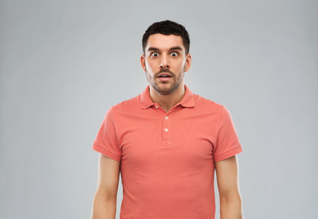 emotion, advertisement and people concept - surprised man in polo t-shirt over gray background Stock Photo