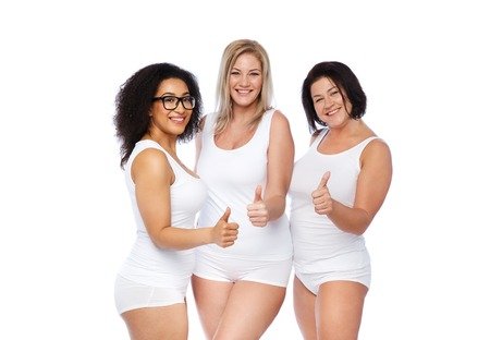 gesture, friendship, beauty, body positive and people concept - group of happy plus size women in white underwear showing thumbs up Stock Photo