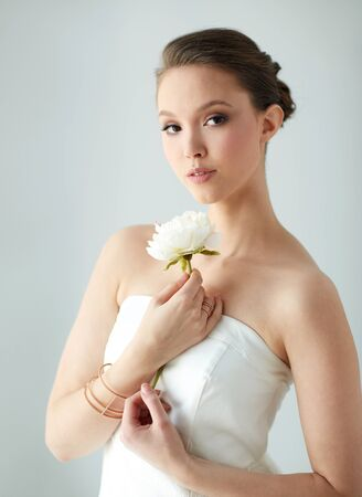 armlet: beauty, jewelry, people and luxury concept - beautiful asian woman or bride in white dress with peony flower, golden ring and bracelet