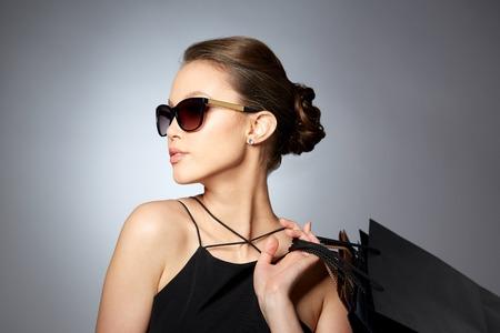 venda, moda, pessoas e conceito de luxo - feliz mulher bonita em óculos de sol pretos com sacolas de compras sobre o fundo cinzento Imagens