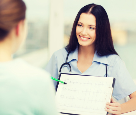 ekg: healthcare and medical concept - female doctor or nurse showing cardiogram to patient Stock Photo
