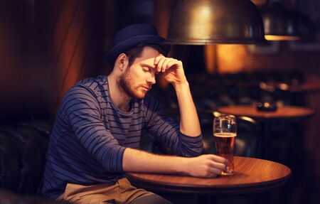 unhappy man: people, loneliness, alcohol and lifestyle concept - unhappy single young man in hat drinking beer at bar or pub