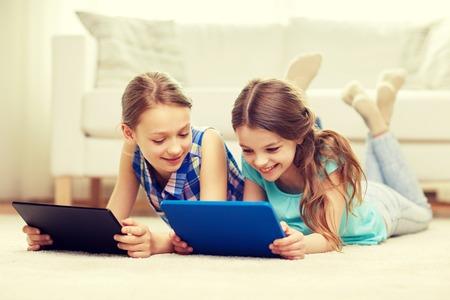 niñas jugando: gente, niños, tecnología, amigos y el concepto de la amistad - niñas felices con las computadoras PC de la tableta tumbado en el suelo en casa