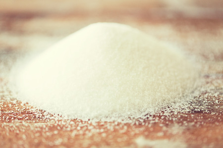 heap up: food, junk-food, cooking and unhealthy eating concept - close up of white sugar heap on wooden table
