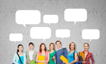 text bubble: education, school and people concept - group of smiling teenage students with folders and school bags over gray brick wall background with empty text bubbles
