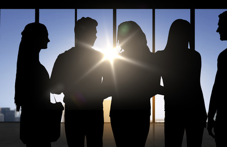 business education: business, education and people concept - people silhouettes over office background Stock Photo
