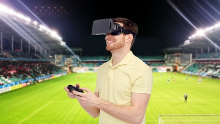 entertainment background: 3d technology, virtual reality, sport, entertainment and people concept - man with virtual reality headset or 3d glasses playing with game controller gamepad over football field on stadium background