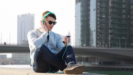 listening to music: la tecnología, los viajes, el turismo y el concepto de la gente - sonriente joven o adolescente en los auriculares con el teléfono inteligente escucha la música sobre Dubai calle de la ciudad de fondo Foto de archivo