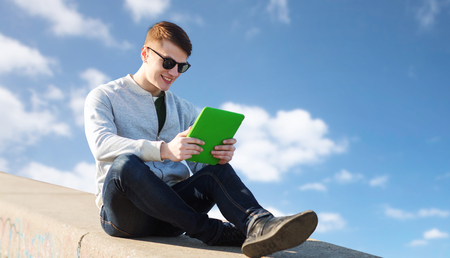 cool gadget: technology, lifestyle and people concept - smiling young man or teenage boy with tablet pc computers over blue sky and clouds background Stock Photo