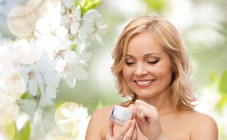 age care: beauty, people, skincare and cosmetics concept - happy woman with cream jar over natural spring cherry blossom background