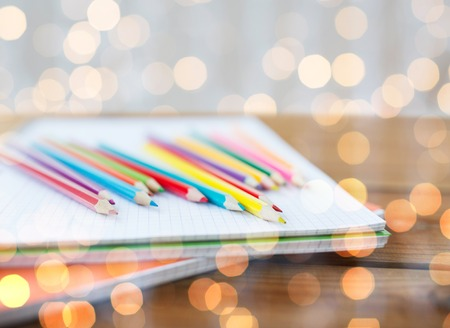 color pencils: school, education, drawing and object concept - close up of crayons or color pencils on notebook paper over holidays lights background