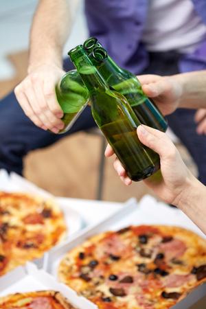 alcoholismo: amistad, el alcohol, la gente, la celebración y el concepto de vacaciones - cerca de las manos masculinas chocan botellas de cerveza y comiendo pizza en casa