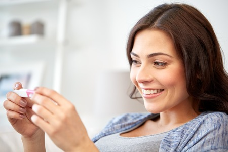 home pregnancy test: pregnancy, fertility, maternity and people concept - happy smiling woman looking at pregnancy test at home