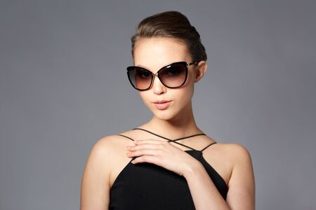 eyewear fashion: accessories, eyewear, fashion, people and luxury concept - beautiful young woman in elegant black sunglasses over gray background