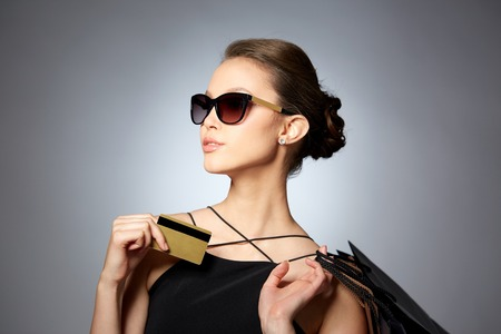 販売、財政、ファッション、人々 および高級コンセプト - クレジット カードとショッピング バッグ灰色の背景の上に黒いサングラスで幸せな美し 写真素材