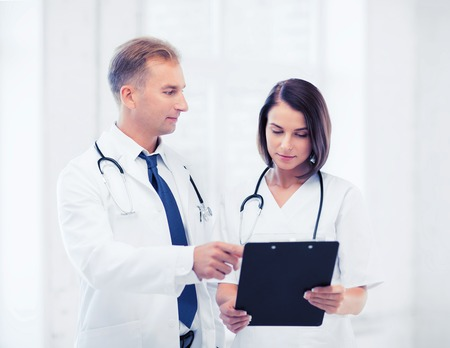 medical doctors: healthcare and medical concept - two doctors discussing diagnosis Stock Photo