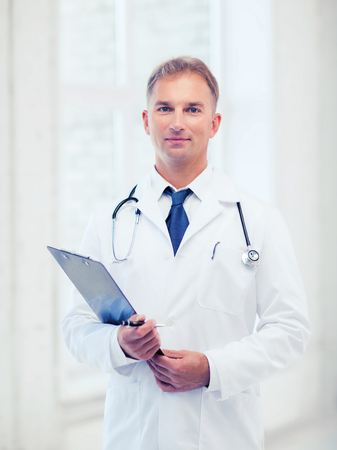 healthcare and medical concept - male doctor with stethoscope and clipboard