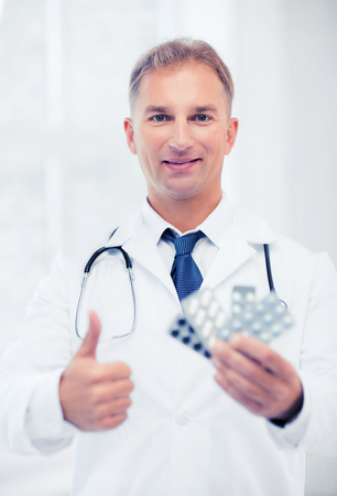 healthcare, medical and pharmacy concept - young male doctor with packs of pills