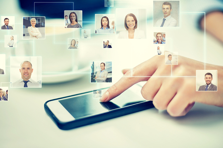 company: business, technology, global communication and people concept - close up of woman hand with smartphone and contact icons projection