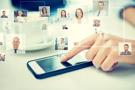 negocios internacionales: negocios, la tecnología, la comunicación global y el concepto de la gente - cerca de la mano de la mujer con el teléfono inteligente y los iconos de contacto de proyección Foto de archivo