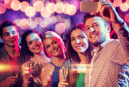 party friends: party, holidays, technology, nightlife and people concept - smiling friends with glasses of champagne and smartphone taking selfie in club